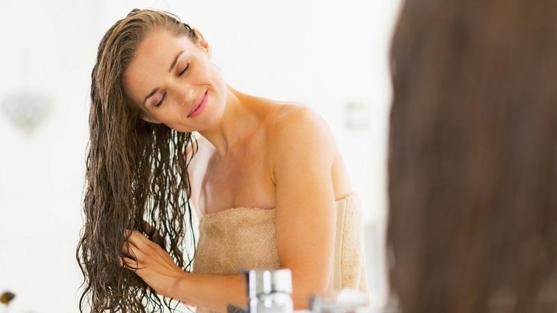 mulher sorridente com cabelo molhado no banheiro